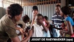 Un militaire angolais administre un vaccin de fièvre jaune à un enfant au marché de 'Quilometro 30' à Luanda, Angola, 16 fevrier 2016. Epa/ JOOST DE RAEYMAEKER