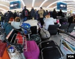 "Para penumpang yang terpaksa ""menginap"" di bandara Heathrow karena penerbangannya dibatalkan."