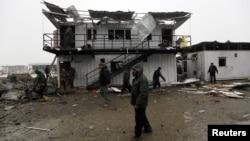 Petugas keamanan Afghanistan memeriksa lokasi kejadian ledakan di Kabul (17/12). Taliban mengaku bertanggung jawab atas pemboman bunuh diri atas perusahaan Amerika, Contrack, yang membangun fasilitas-fasilitas untuk pangkalan militer di negara itu.
