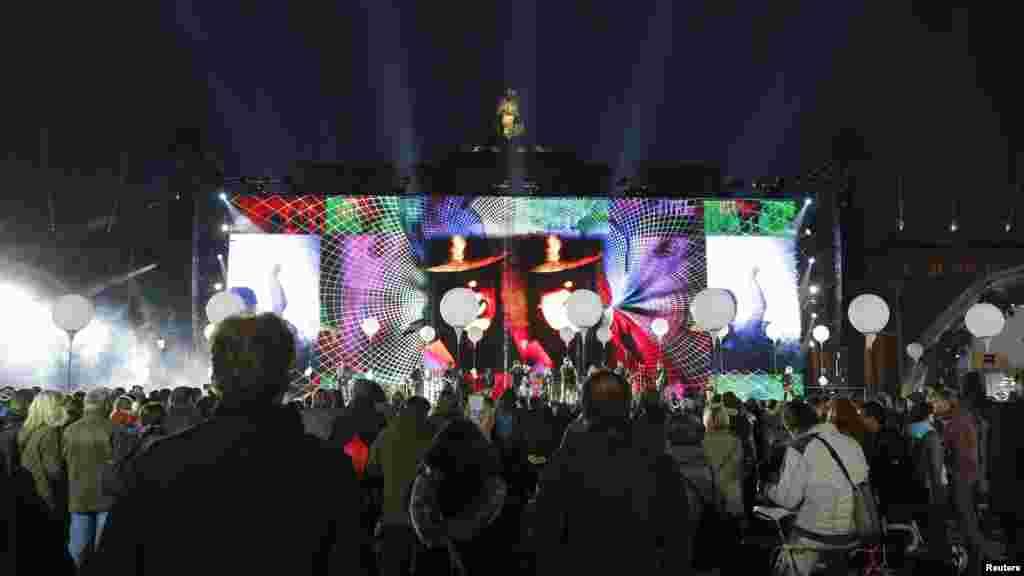 رهگذران هنگام عبور از دروازه برندنبرگ، به موسیقی زنده گوش میکنند - ۱۶ آبان ۱۳۹۳