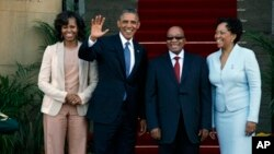 Presidente Barack Obama ladeado pela Primeira Dama Michelle Obama, Esq, acena com o Presidente sul africano Jacob Zuma.