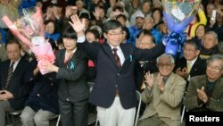 FILE - Mayor Susumu Inamine, center, flanked by his wife, Ritsuko, celebrates his re-election in Nago, Okinawa, Jan. 19, 2014. Inamine, who is opposed to a U.S. Marines base on Okinawa, seeks another term in an election Feb. 4, 2018.