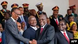 Tanzania's newly elected president John Magufuli (2ndR) shakes hands with Rwanda's president Paul Kagame (L) eyed by Zimbabwe's president Robert Mugabe (R) and Uganda's president Yoweri Museveni (2ndL) during the swearing in ceremony in Dar es Salaam, on Nov. 5, 2015.