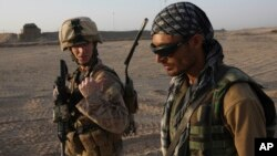FILE - U.S. Marine 1st Lt. Zachary Bennett talks with an Afghan interpreter during a joint patrol in Helmand province, southern Afghanistan, Sept. 19, 2009.