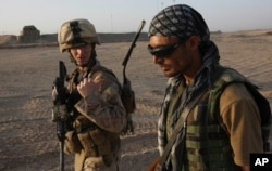 FILE - A U.S. Marine talks with an Afghan interpreter during a joint patrol in Helmand province, southern Afghanistan, Sept. 19, 2009. Faisal Razmal worked as an interpreter for U.S. forces in Afghanistan for five years prior to coming to the U.S. under a Special Immigrant Visa (SIV) program.