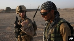 FILE - U.S. Marine 1st Lt. Zachary Bennett talks with Afghan interpreter during a joint patrol in Helmand province, southern Afghanistan.