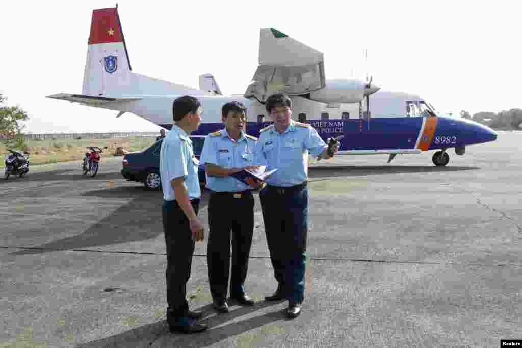 Thượng tá Đỗ Đức Minh, Phó Tham mưu trưởng Quân chủng Phòng không không quân (phải) nói chuyện với các nhân viên trước máy bay CASA 212 chuẩn bị cất cánh trong phi vụ tìm kiếm máy bay Malaysia bị mất tích, ngày 12/3/2014.