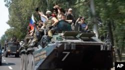 Pemberontak pro-Rusia mengendarai tank mereka di Donetsk.