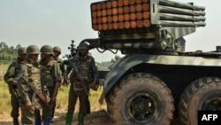 Des soldats des Forces armées de la République démocratique du Congo (FARDC) se tiennent près d'un lance-roquettes multiples mobile à Matombo, à 35 km au nord de Beni, au Nord-Kivu, le 13 janvier 2018.