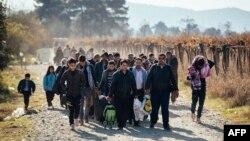 FILE - Migrants and refugees are seen walking after crossing the Greek-Macedonian border near Gevgelija, Nov. 16, 2015.