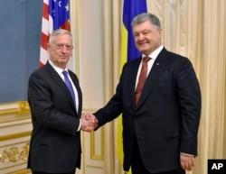 Ukrainian President, Petro Poroshenko, right, and U.S. Defense Secretary James Mattis shake hands during a meeting in Kyiv, Ukraine, Aug. 24, 2017.