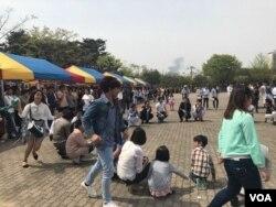ពលករកម្ពុជាលេងល្បែងប្រជាប្រិយនៅសួន Manseok Park ក្នុងក្រុង Suwon ប្រទេសកូរ៉េខាងត្បូង កាលពីថ្ងៃអាទិត្យ ទី១៦ ខែមេសា ឆ្នាំ២០១៧។ (សុខ ខេមរា/VOA)