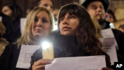 Romanian magistrates stand holding copies of their professional oath during a silent protest outside the Bucharest Court of Appeal in Bucharest, Romania, Dec. 18, 2017.