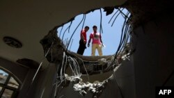 Warga melongok ke dalam lubang di atap sebuah rumah yang hancur akibat serangan udara koalisi pimpinan Saudi dekat bukit Fajj Attan di ibukota Sana'a, Yaman. (Foto: Dok)