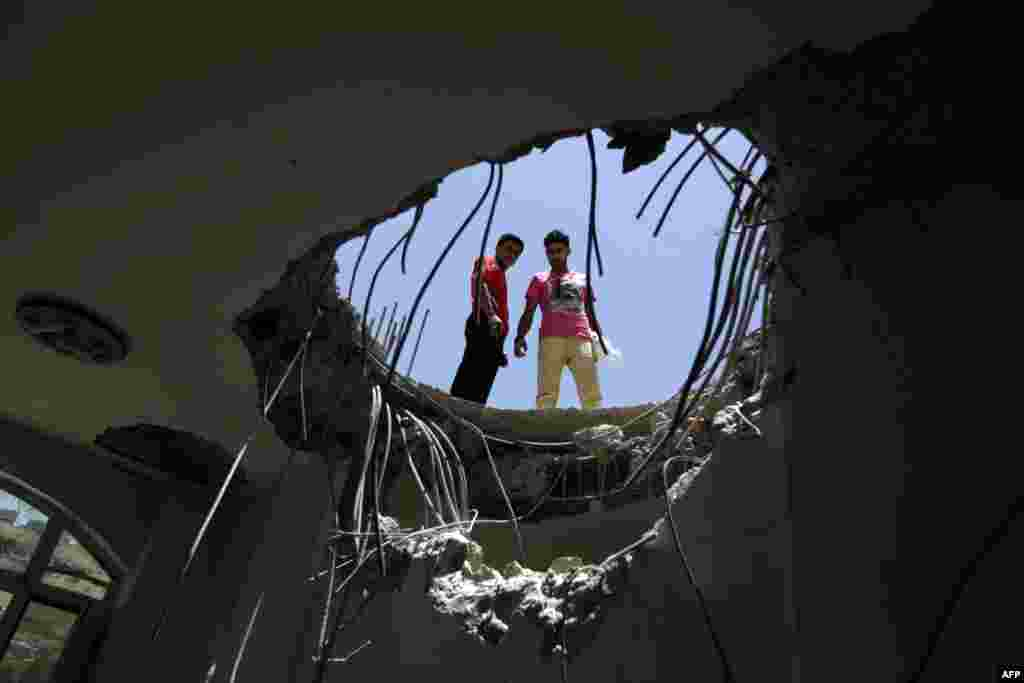 Yemenis look down through a hole in the roof of a house which was damaged the day before during an air strike by Saudi-led coalition warplanes on the nearby base on Fajj Attan hill in the capital Sanaa.
