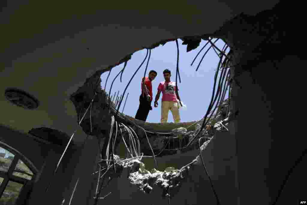Warga Yaman melihat ke dalam lubang di atap sebuah rumah yang rusak satu hari sebelum serangan udara yang dipimpin oleh pesawat perang Arab Saudi di pangkalan di bukit Fajj Attan, Sanaa.