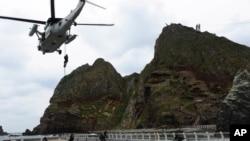 Các thành viên của lực lượng hải quân nhảy xuống từ trực thăng UH-60 trong một cuộc tập trận ở đảo Dokdo, Nam Triều Tiên.