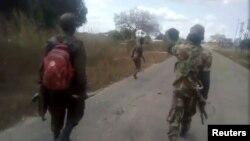 Uma mulher nua é perseguida por homens vestidos com farda militar, junto à vila de Diaca, em Cabo Delgado, Moçambique
