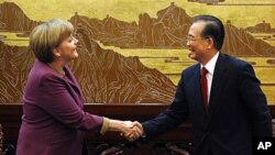 German Chancellor Angela Merkel (L) shakes hands with Chinese Premier Wen Jiabao before a news conference in the Great Hall of the People in Beijing, February 2, 2012.