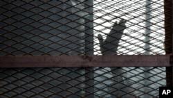 Un accusé est aperçu dans une cage, dans une salle d'audience, à la prison Torah, dans le sud du Caire, Egypte, 22 août 2015.