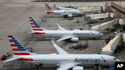 FILE - American Airlines planes arrive at Phoenix Sky Harbor International Airport in Phoenix, July 17, 2019. The airline said two labor unions ignored a judge's order to quickly end a work slowdown by mechanics.
