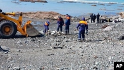 In this photo released by the Russian Emergency Ministry Press Service, emergency personnel work near the site where a helicopter carrying tourists crashed at Kurile Lake in the Kronotsky nature reserve on the Kamchatka Peninsula in Russia, Aug. 12, 2021.