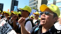 FILE - Taiwanese workers shout slogans during a protest in Taipei, Taiwan, Jan. 4, 2020. Hundreds of workers from various labor groups staged a protest before general elections demanding for better conditions for workers.