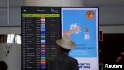 FILE - A man checks departure information on a display screen at Faro airport amid the coronavirus disease (COVID-19) pandemic, in Faro, Portugal, June 6, 2021.