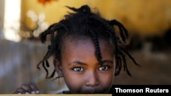 FILE - An Ethiopian girl stands at the window of a temporary shelter, at the Village 8 refugees transit camp, which houses Ethiopian refugees fleeing the fighting in the Tigray region, near the Sudan-Ethiopia border.