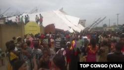 Les voisins s'assemblent sur les lieux de l'accident où un immeuble de cinq étages s'est écroulé, à Kinshasa, RDC, 26 octobre 2016. VOA/TOP CONGO