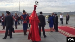 A Mongolian woman dressed in red traditional deel with LV shoes greets US Secretary of State John Kerry as her arrives in Ulaanbaatar, Mongolia. (N. Ching/VOA)