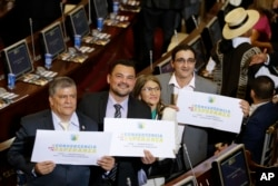 """From left, Olmedo Ruiz, Sergio Marin, Sandra Ramirez and Jairo Quintero, all former members of the demobilized Revolutionary Armed Forces of Colombia, hold signs reading """"Convergence for hope"""" at Congress before taking seats in the lower chamber of the newly elected legislature, in Bogota, Colombia, July 20, 2018."""