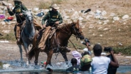 FILE - U.S. Customs and Border Protection mounted officers attempt to contain migrants as they cross the Rio Grande from Ciudad Acuña, Mexico, into Del Rio, Texas, Sept. 19, 2021.