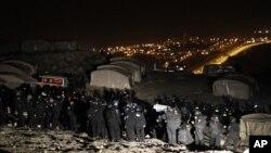 Polisi perbatasan Israel terlihat tengah mengusir aktivis Palestina dari tenda-tenda yang mereka dirikan di lokasi yang dikenal sebagai E1, dekat Yerusalem, 13 Januari 2013. (REUTERS/Ammar Awad). Petugas keamanan Israel dikabarkan telah mengevakuasi sekitar 100 orang Palestina, Minggu pagi dari wilayah tersebut.