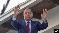 FILE - Former dictator Jean-Claude 'Baby Doc' Duvalier waves to supporters from the balcony of a rented guest house where he is staying in Port-au-Prince.