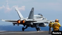 A U.S. Navy F/A-18 Hornet aircraft takes off during a tour of the USS Nimitz aircraft carrier on patrol in the South China Sea, May 23, 2013.