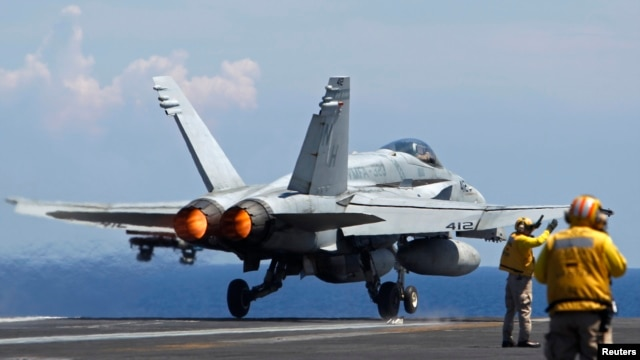FILE - A U.S. Navy F/A-18 Hornet aircraft takes off during a tour of the USS Nimitz aircraft carrier on patrol in the South China Sea May 23, 2013.