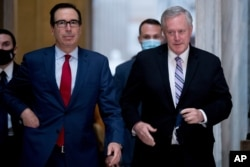Treasury Secretary Steven Mnuchin, left, and White House Chief of Staff Mark Meadows, right, walk out of a meeting with House Speaker Nancy Pelosi and Senate Minority Leader Sen. Chuck Schumer, Aug. 7, 2020.
