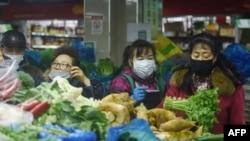 中国浙江省杭州市的一家超市里顾客戴着口罩购买蔬菜。(2020年2月9日)