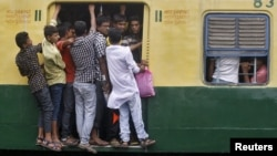 FILE - Commuters stand at an open doorway of a suburban train during the morning rush hour in Kolkata, India, July 31, 2015. India is set to overtake China and become the world's most populous country in less than a decade - six years sooner than previously forecast, the United Nations said in 2015.