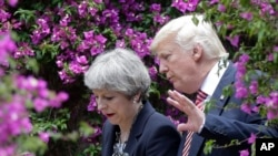 FILE - U.S. President Donald Trump talks with British Prime Minister Theresa May in Taormina, Italy.