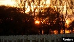 在2018年11月8日法国阿兰-圣纳泽尔的洛雷特圣母院墓地举行的仪式上,太阳落在墓碑后面,作为第一次世界大战纪念之旅的一部分。