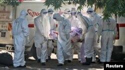 Các tình nguyện viên khiêng thi thể người chết vì virus corona trong một đám tang tại một nghĩa trang ở Mandalay, Myanmar, ngày 14 tháng 7, 2021.