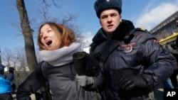 Полицейский арестовывает активистку антифашистского движения. Санкт-Петербург. Россия. 22 марта 2015 г.