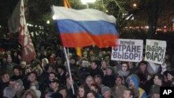 """反對現俄羅斯政府的抗議者星期一在莫斯科集會。圖中的標語說﹕""""這次選舉是鬧劇""""﹔""""還國家選擇的權利""""。"""