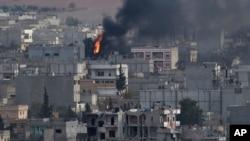 Kebakaran di kota Kobani, Suriah, dilihat dari atas bukit di luar kota Suruc, perbatasan Turki dan Suriah (13/11).