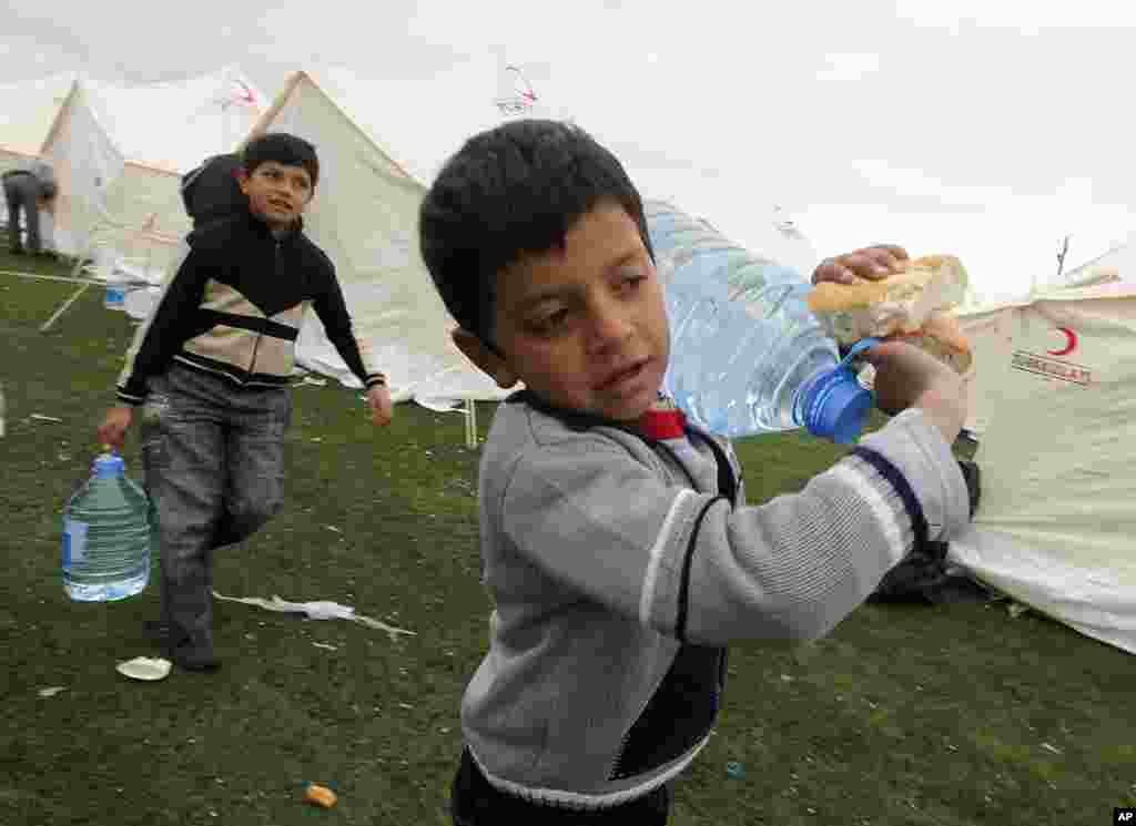 Earthquake survivors carry bottles of water back to their tent after receiving food aid in Ercis, near the eastern Turkish city of Van, October 27, 2011. (Reuters)