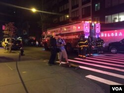 A police officer gives instructions to a passer-by as other police and fire crews work near the scene of an explosion in Manhattan's Chelsea neighborhood, Sept. 17, 2016. (C. Mendoza/VOA)