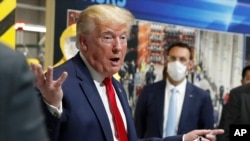 FILE - In this May 21, 2020 file photo, President Donald Trump holds a face mask in his left hand as he speaks during a tour of Ford's Rawsonville Components Plant that has been converted to making personal protection and medical equipment, in…