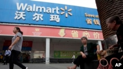 FILE - Residents walk past a Wal-Mart in Shenzhen, in southern China's Guangdong province.